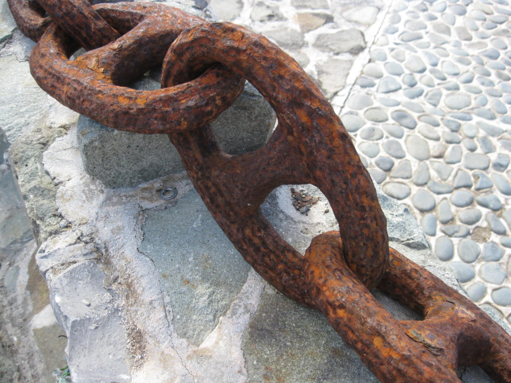 large rusted chain on cobblestones