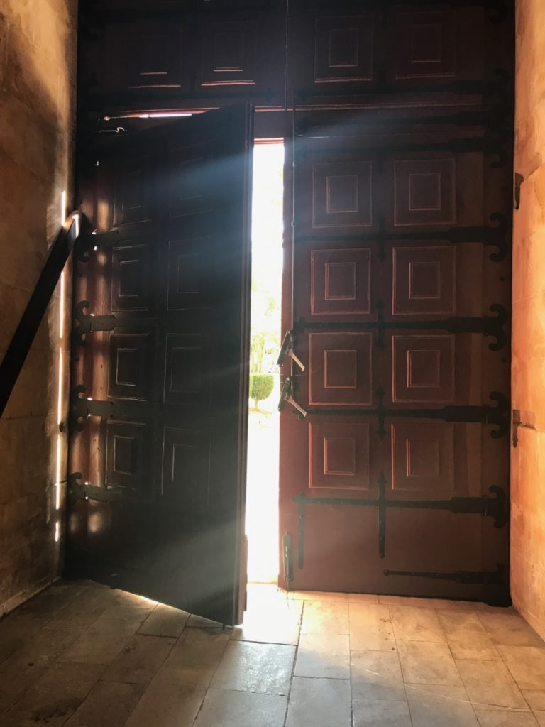 heavy door ajar with light streaming in