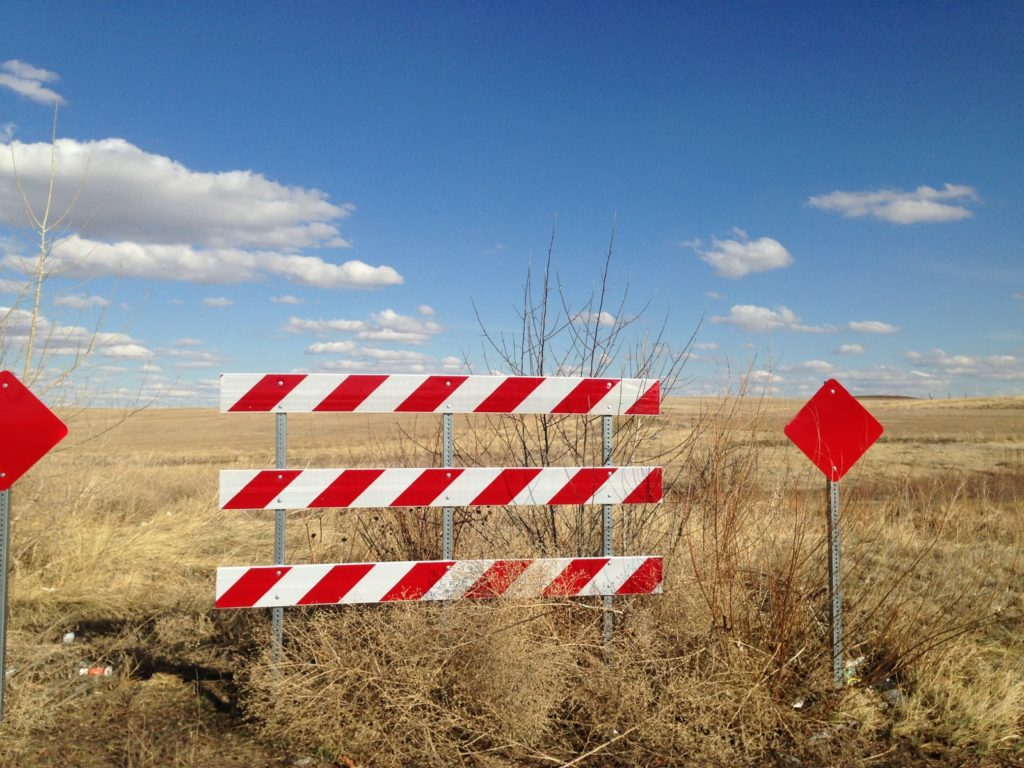 red and white road-closed barrier
