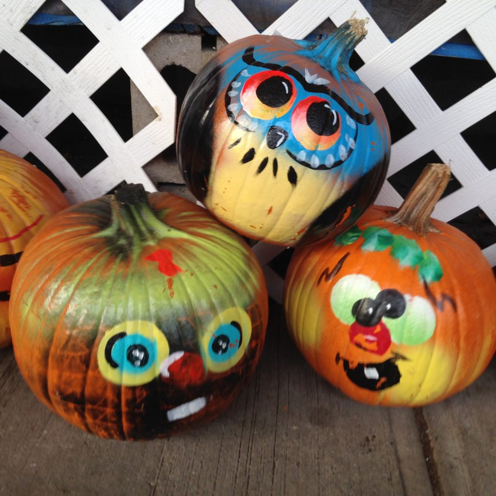 3 pumpkins painted with funny faces